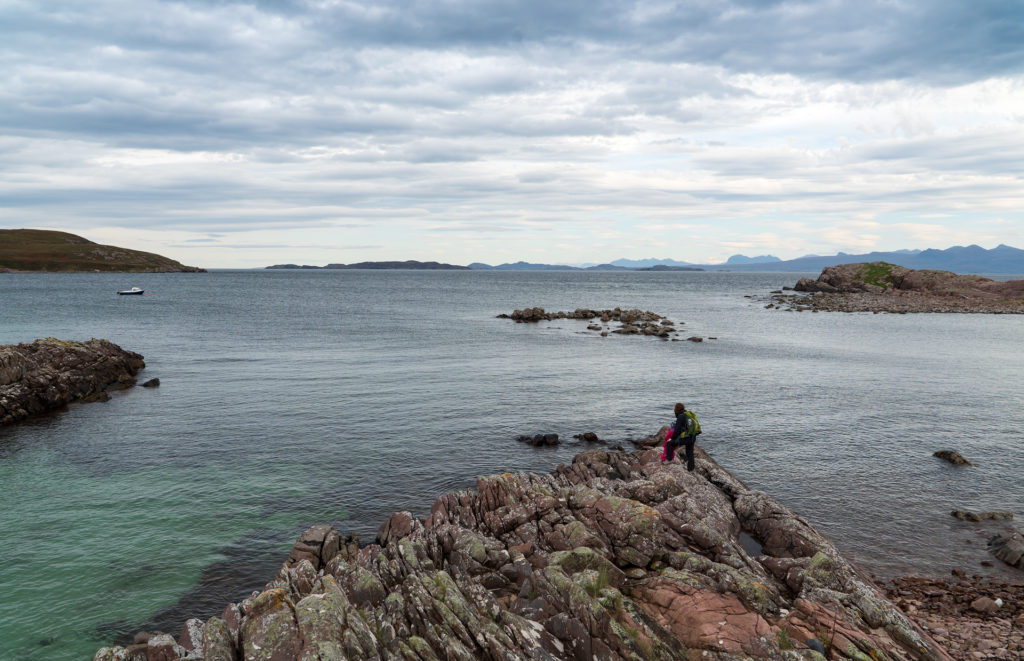 Isle of Lewis - Bild zeigt im Vordergrund einen Felsen mit zwei Personen die auf das Meer blicken. Schottland