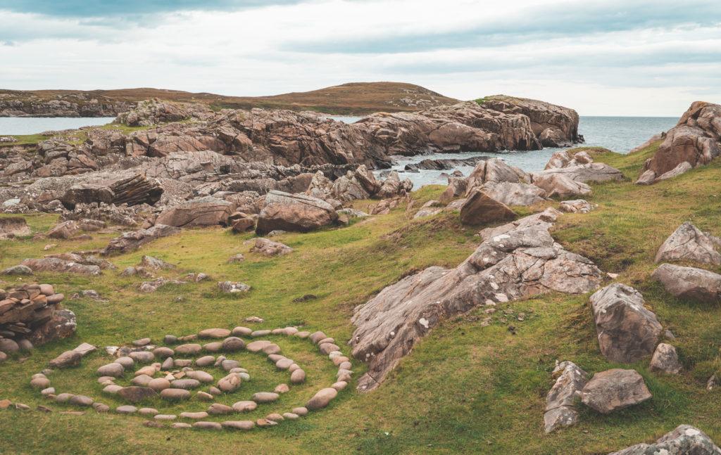 Isle of Lewis - Abbildung zeigt einen Steinkreis im Gras vor einer felsigen Küste auf den äußeren Hebriden