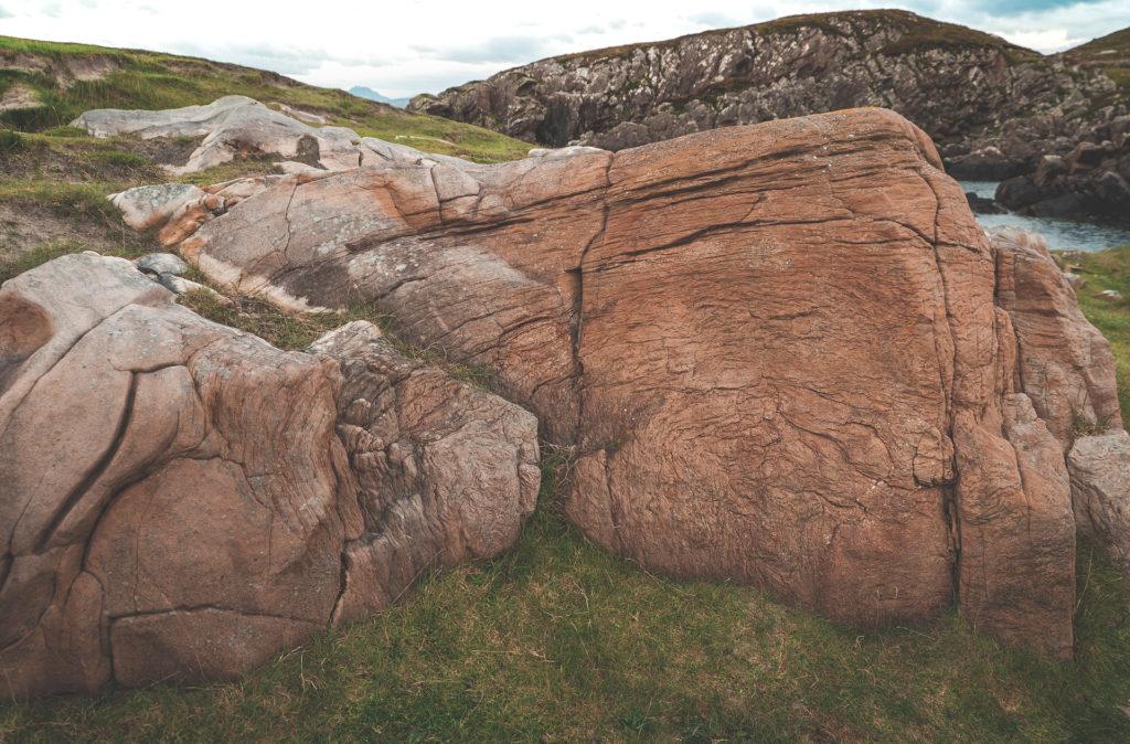 Isle of Lewis - Bild zeigt einen strukturierten, rötlichen Felsen im Gras. Im Hintergrund sieht man ein Stück Meer und Felsen. Äußere Hebriden