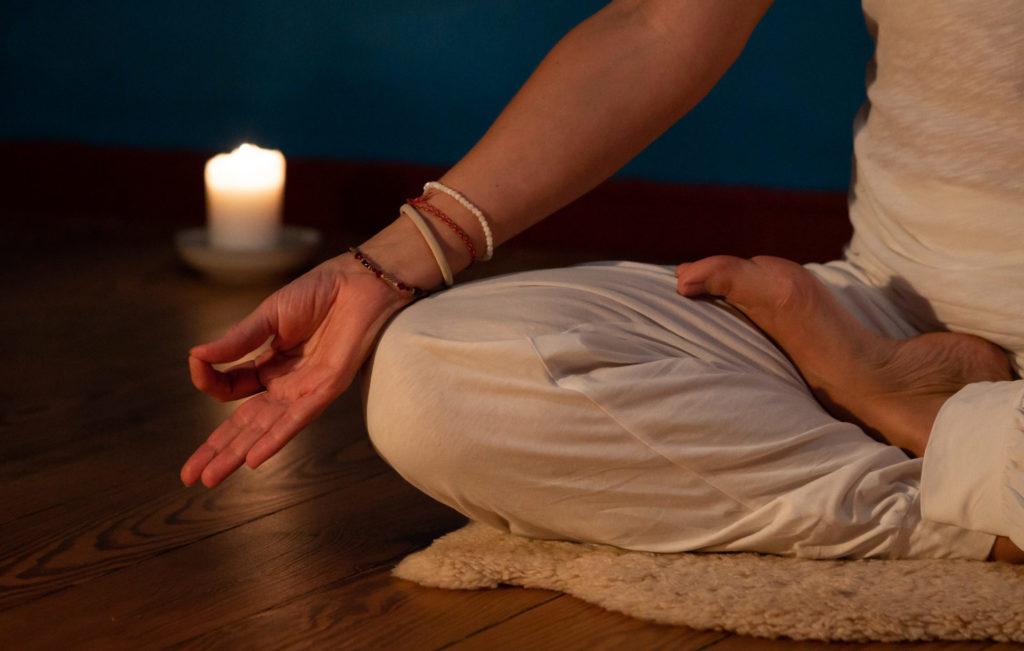 Yoga-Fotografie einer Frau im Yogasitz im Vordergrund. Im Hintergrund sieht man eine brennende Kerze